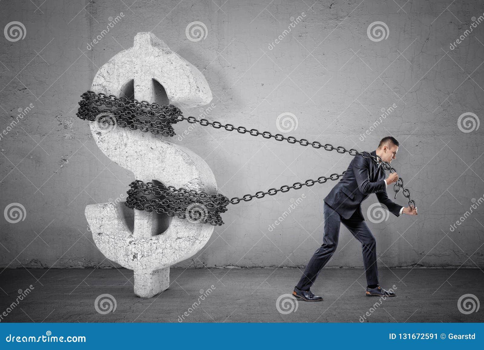 Biznesmen próbuje ruszać się wielkiego betonowego dolarowego znaka od swój miejsca pociąga przy łańcuchem