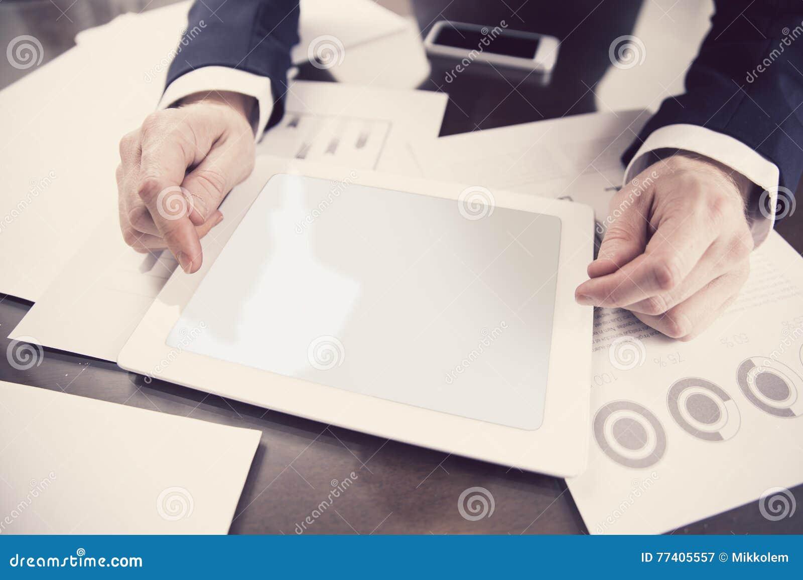 Biznesmen pracuje z cyfrową pastylką przy biurem