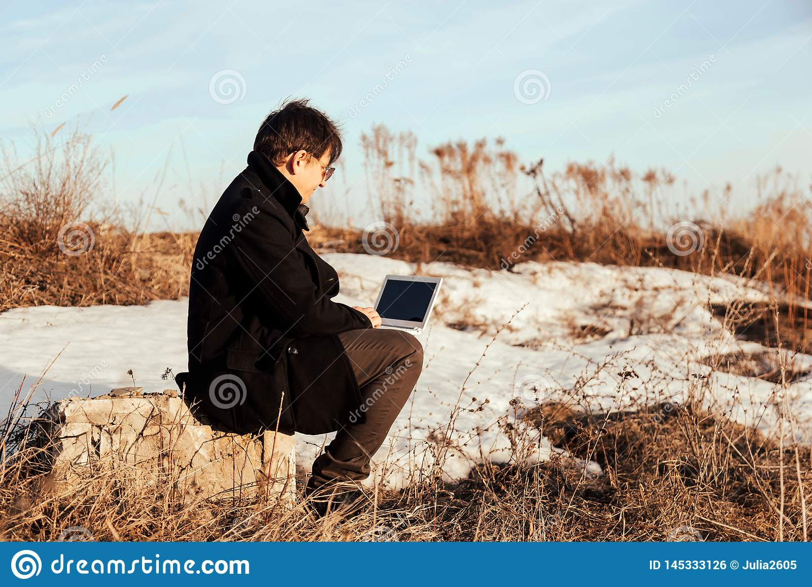 Biznesmen pracuje z jego laptopem outside