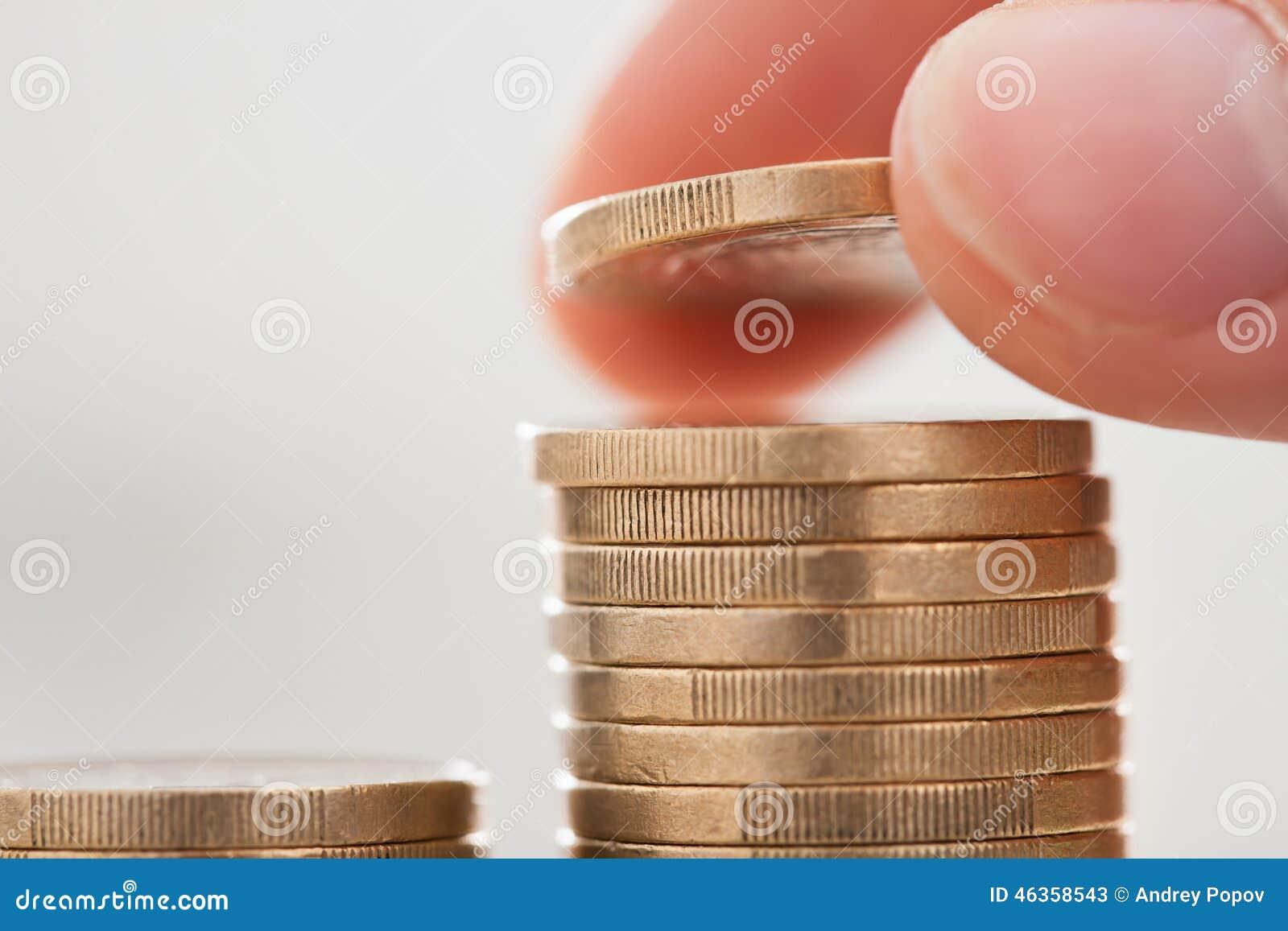Biznesmen ręki sztaplowania monety w biurze