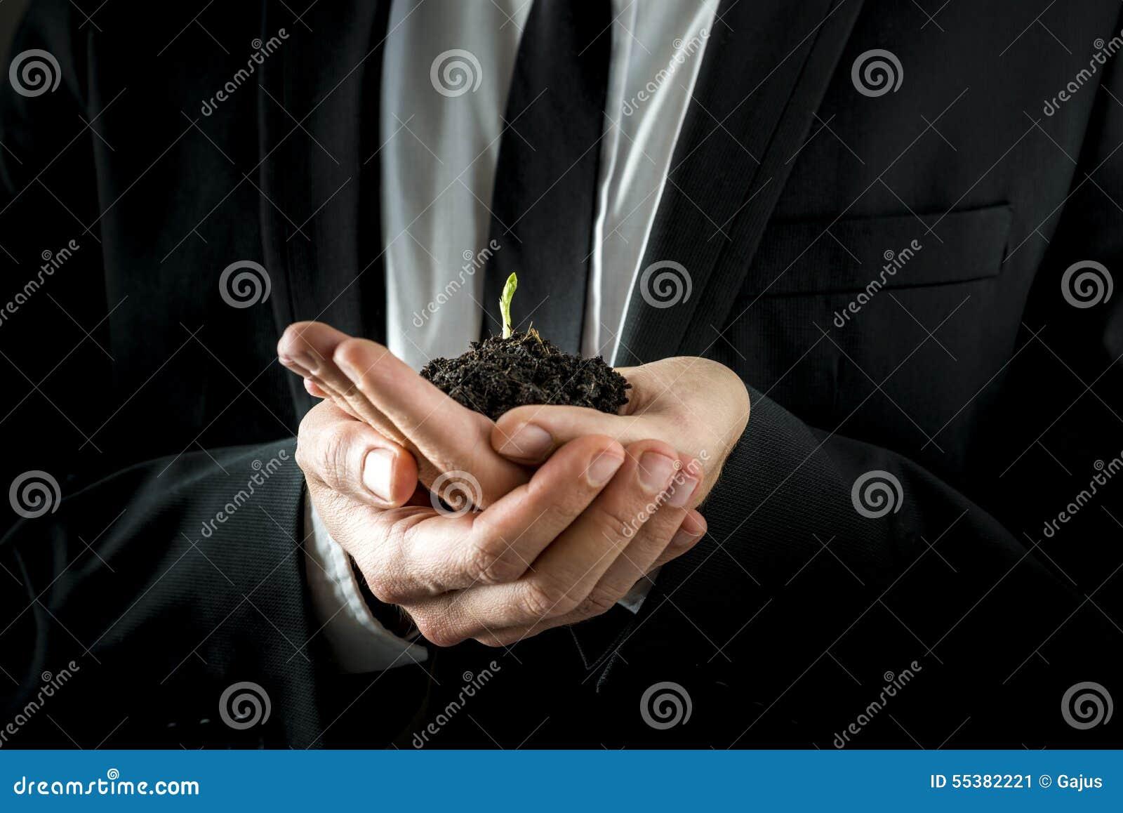 Biznesmen ręki Trzyma Glebowymi z potomstwo flancą
