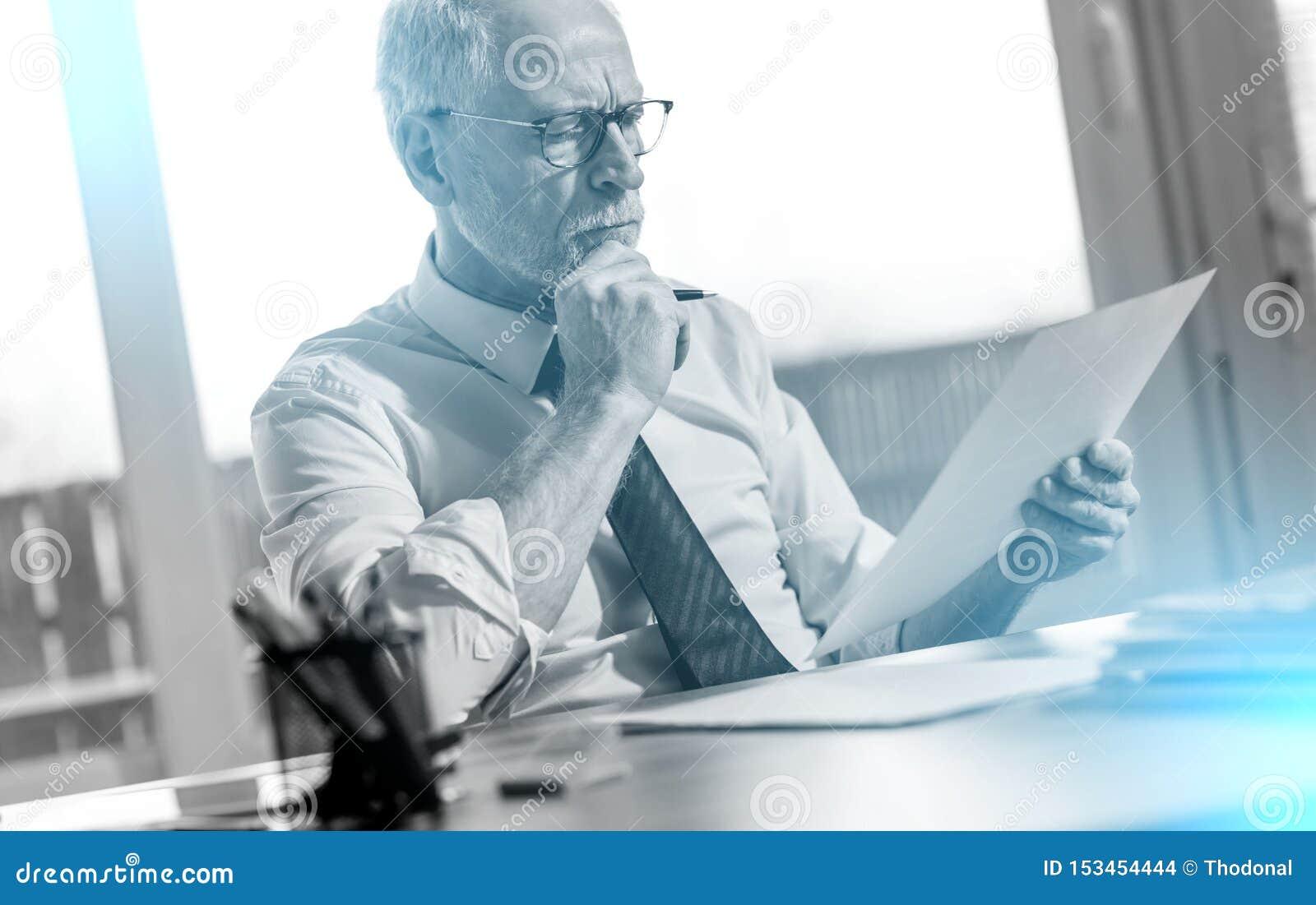 Biznesmen sprawdza dokument; lekki skutek