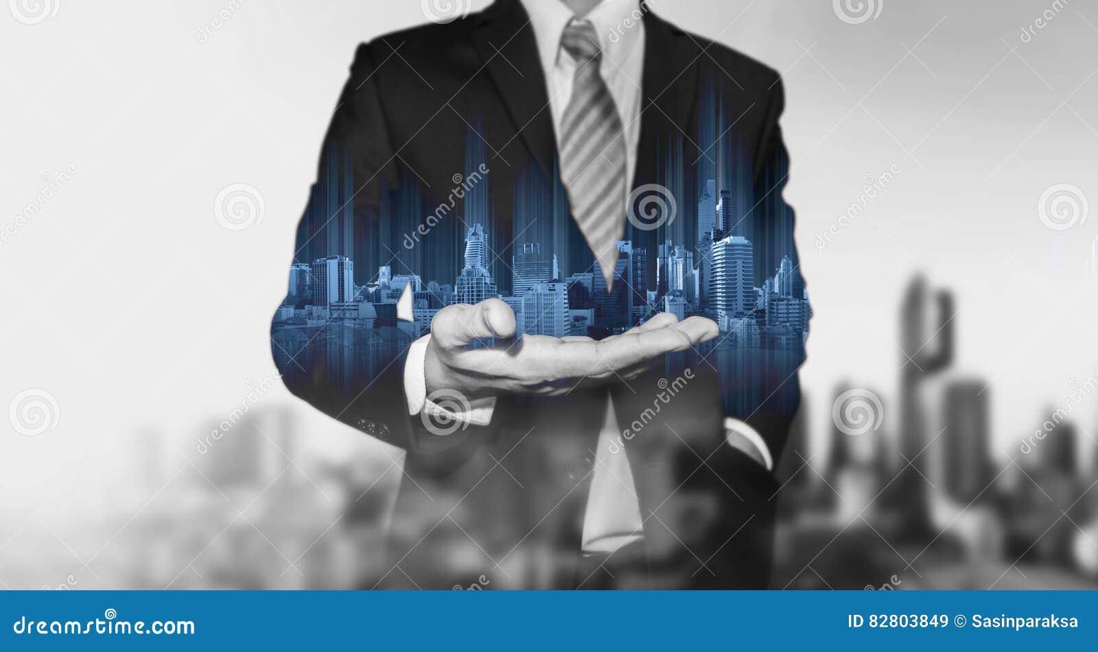 Biznesmen trzyma błękitnego nowożytnego budynku hologram na ręce, z czarny i biały miasta tłem