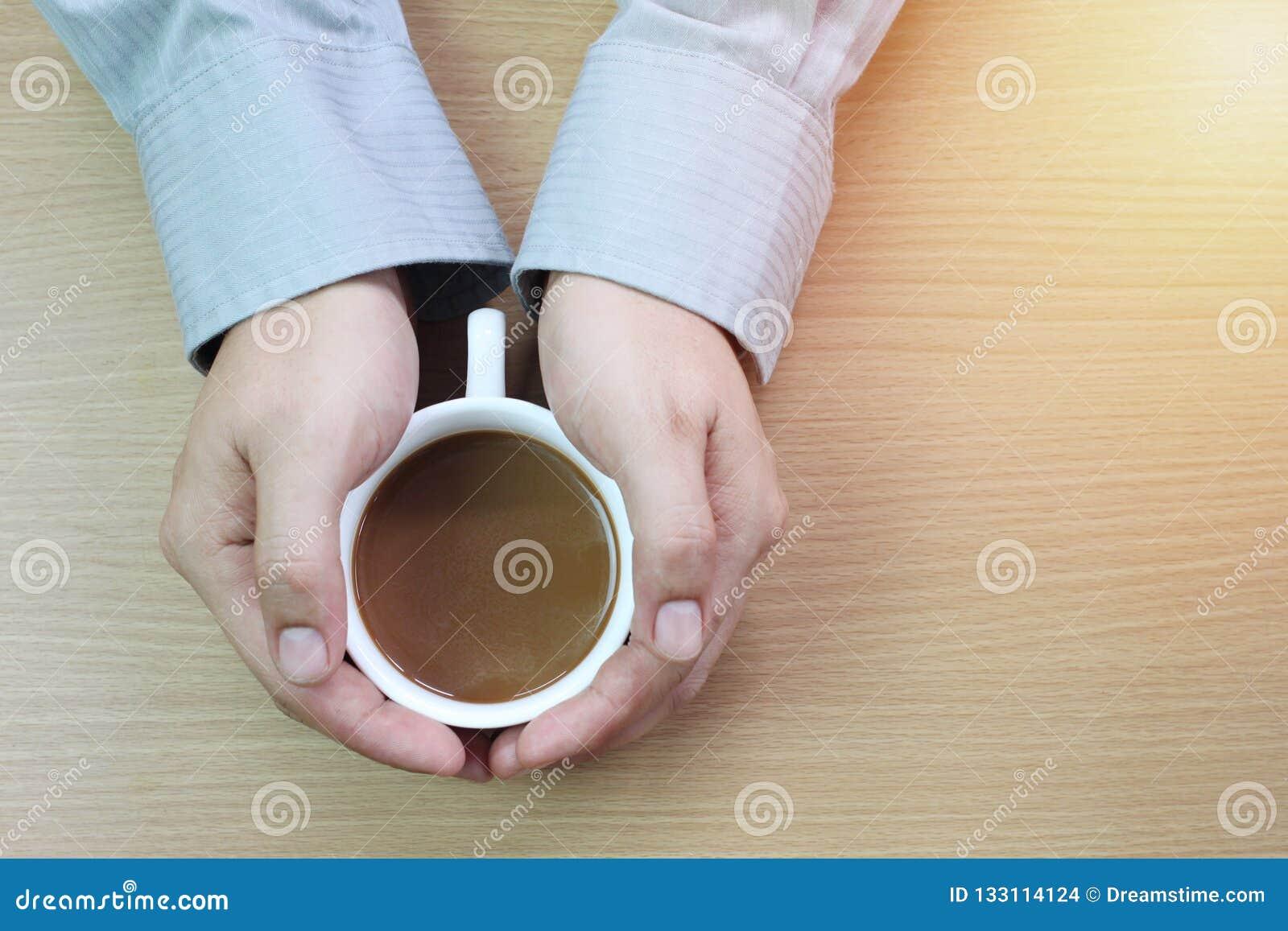 Biznesmen trzyma białego kawowego kubek