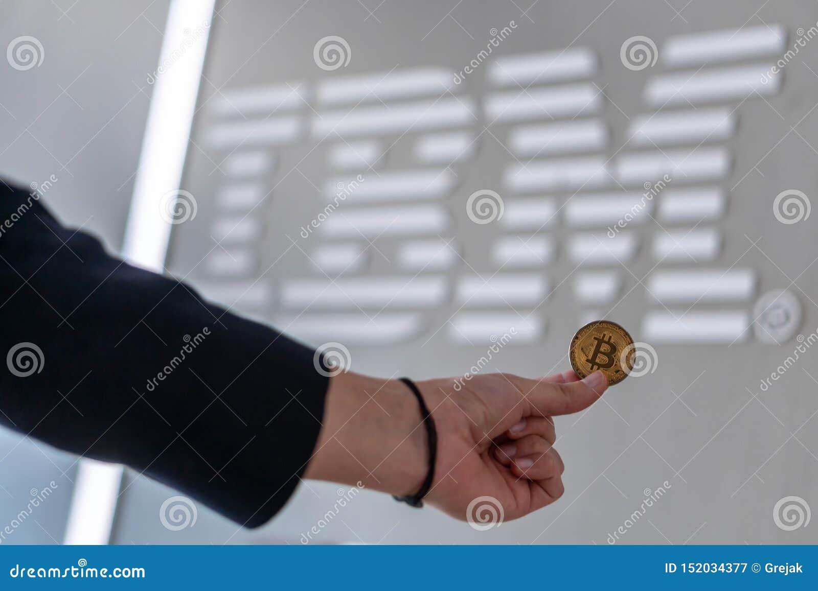 Biznesmen trzyma Bitcoin monetę Slovenia, Luty z IBM logo na laptopu ekranie, - 26th, 2019