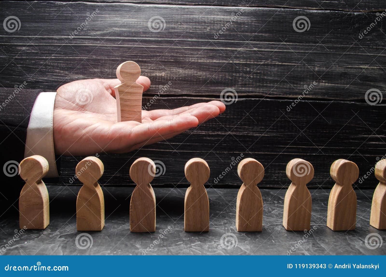 Biznesmen trzyma drewnianego lidera postać na palmie jego oddawał liczbę inni pracownicy Pojęcie lider, drużynowa praca