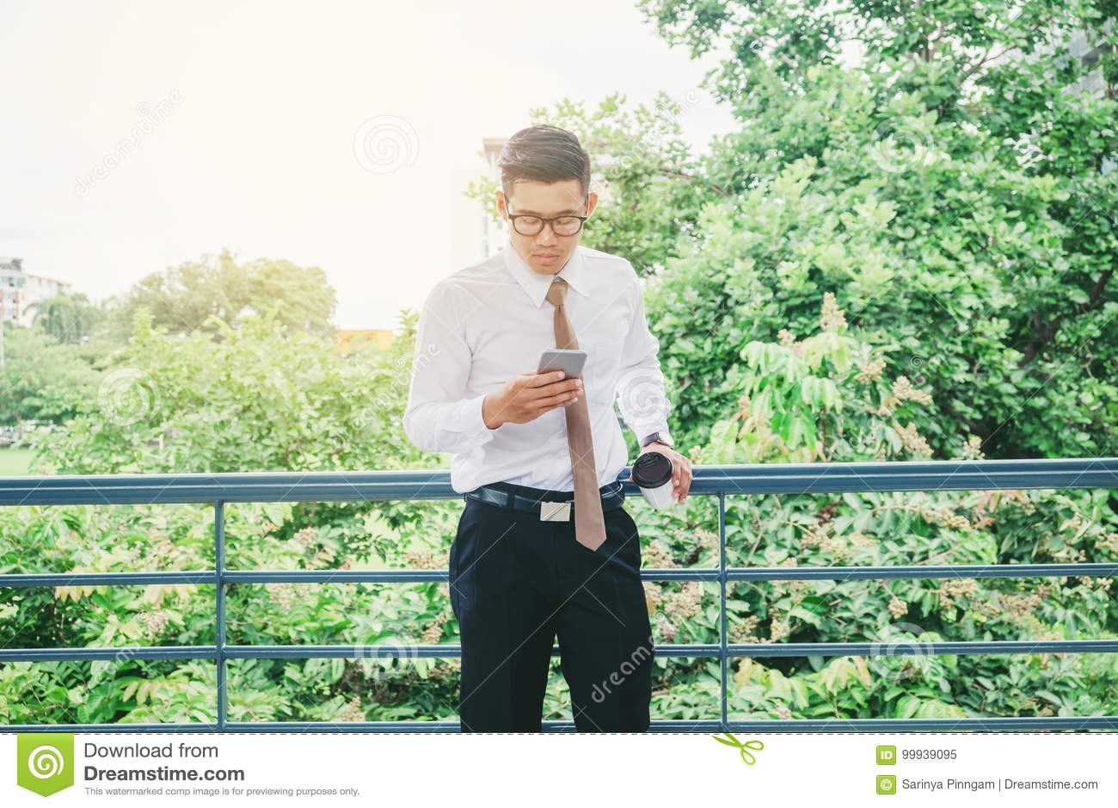 Biznesmen Używa telefon komórkowy rękę trzyma filiżankę plenerowa