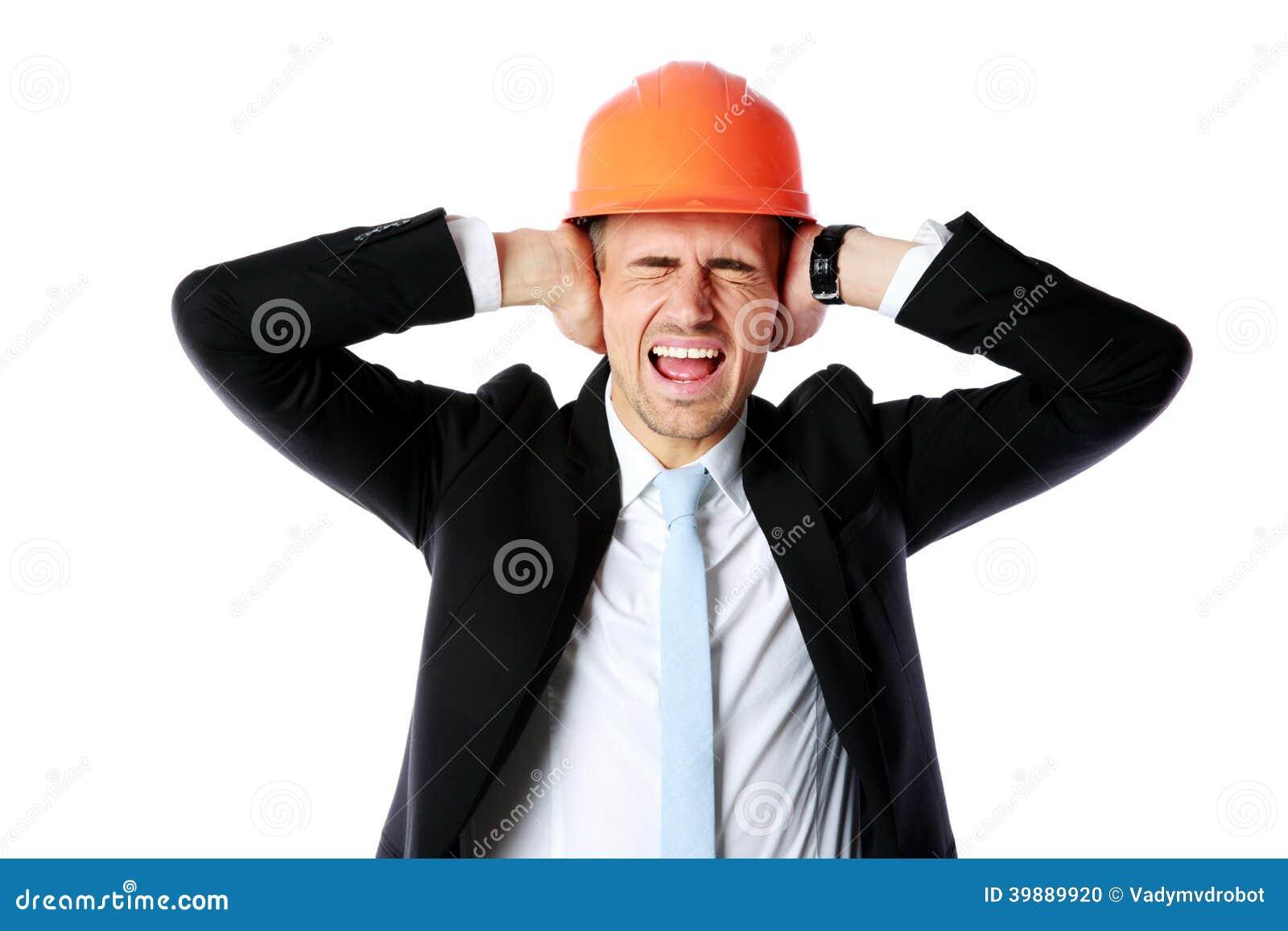 Biznesmen w hełmie zakrywa jego ucho