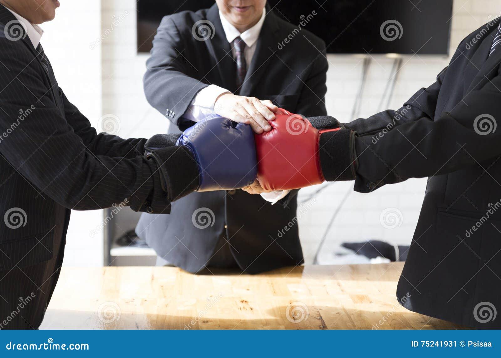 Biznesmen w kostiumu z czerwonymi i błękitnymi bokserskimi rękawiczkami