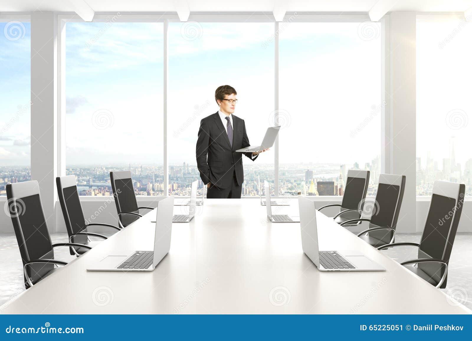 Biznesmen w nowożytnej sala konferencyjnej z meble, laptopy