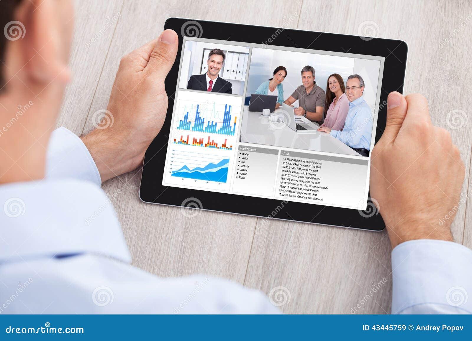 Biznesmen wideo konferencja z drużyną na cyfrowej pastylce