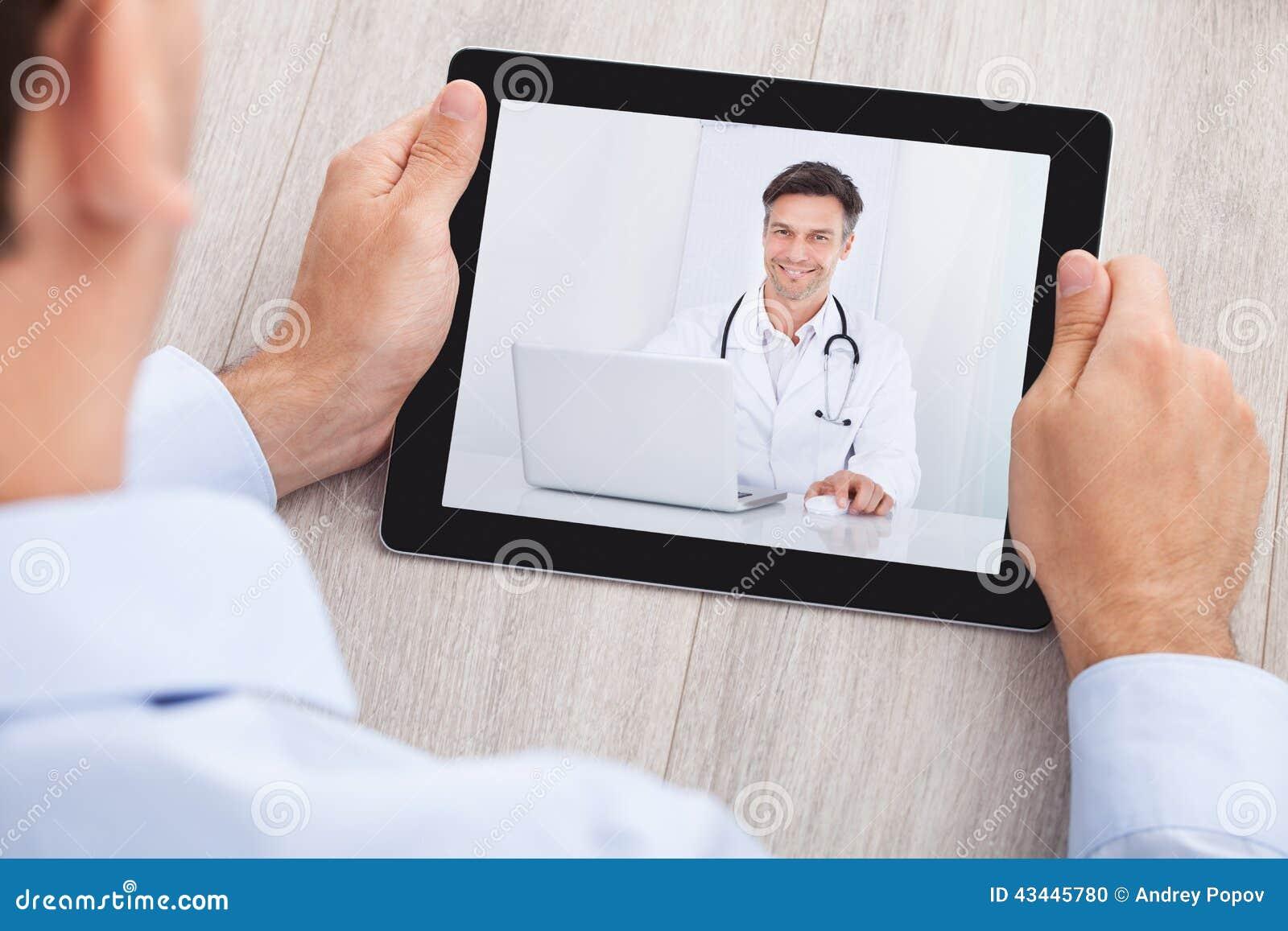 Biznesmen wideo konferencja z lekarką na cyfrowej pastylce