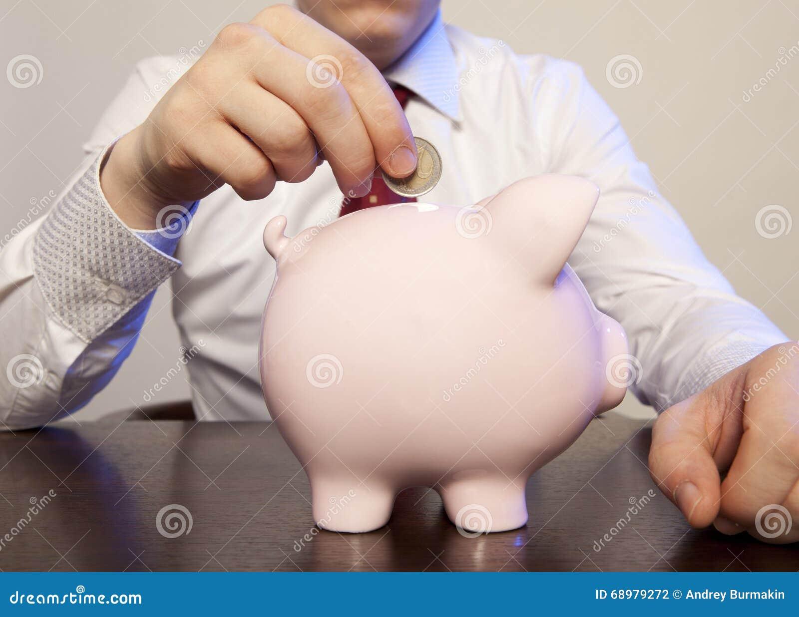 Biznesmen z różowym prosiątko bankiem