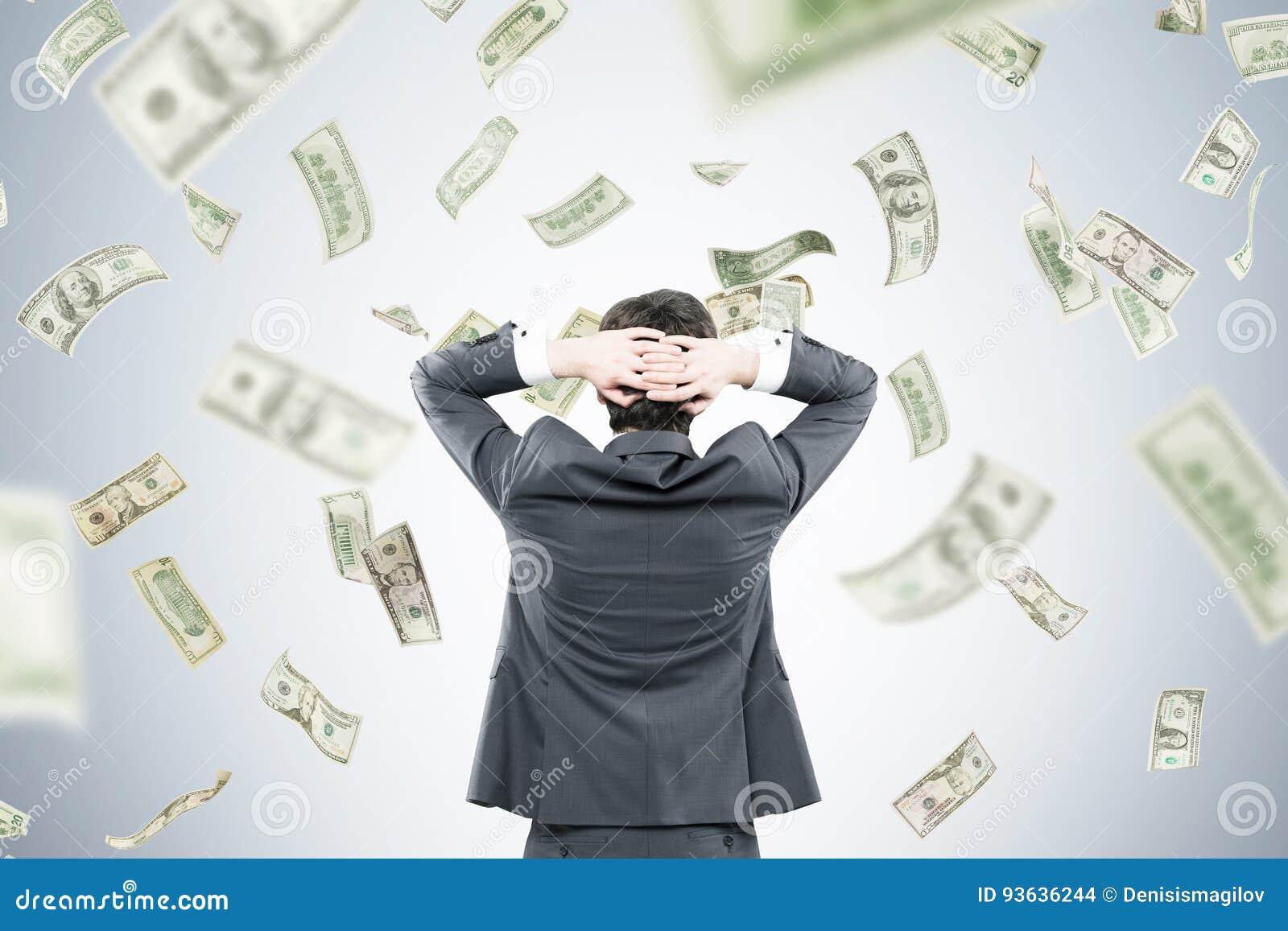 Biznesmen z rękami za głową w pieniądze przepływie