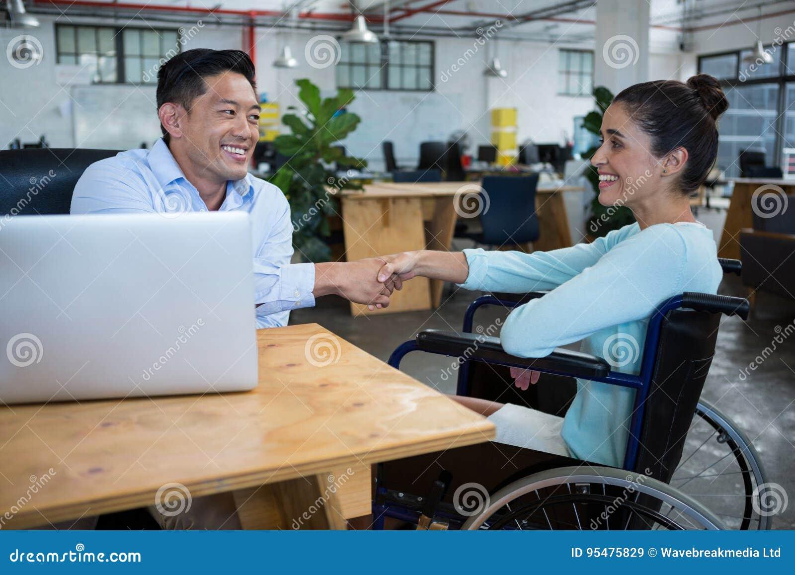 Biznesmena chwiania ręki z niepełnosprawnym kolegą