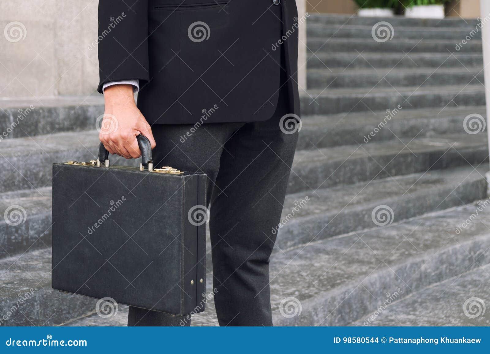 Biznesmena mienie i pozycja teczka w ręka pracującym dowcipie
