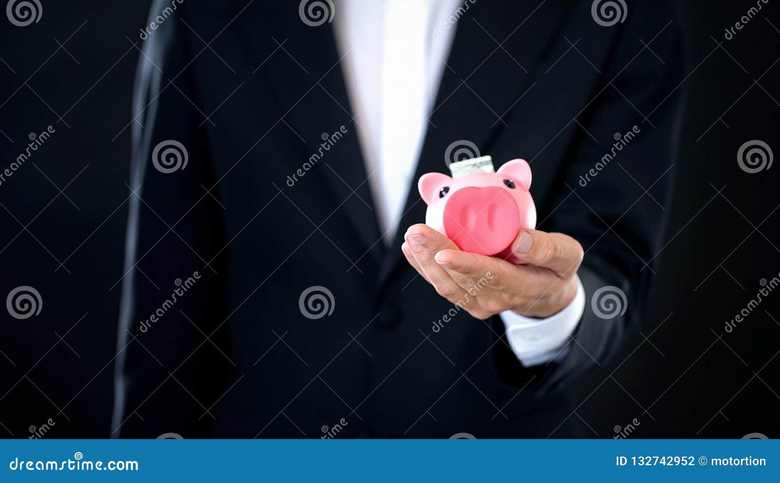 Biznesmena mienie w ręki piggybank z dolarowym banknotem wśrodku, oszczędzania