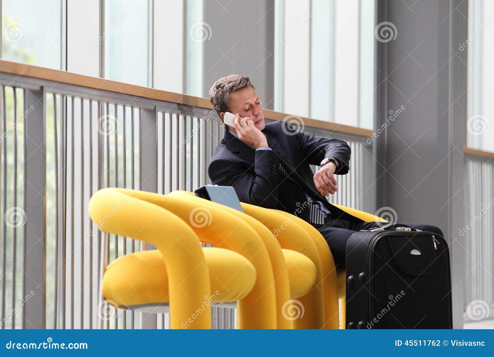 Biznesmena obsiadanie opowiada na telefonie na biznesowej podróży,