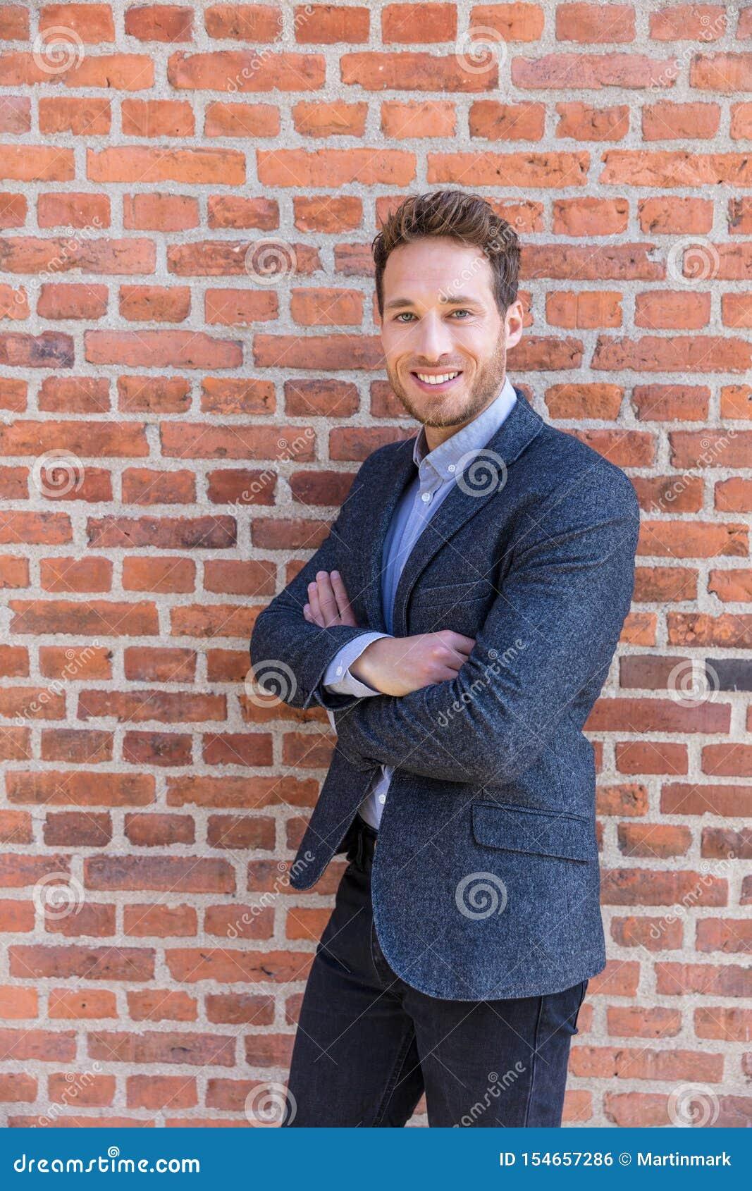 Biznesmena portret na ściany z cegieł tle Młode ufne uśmiechnięte mężczyzna pozycji ręki krzyżować