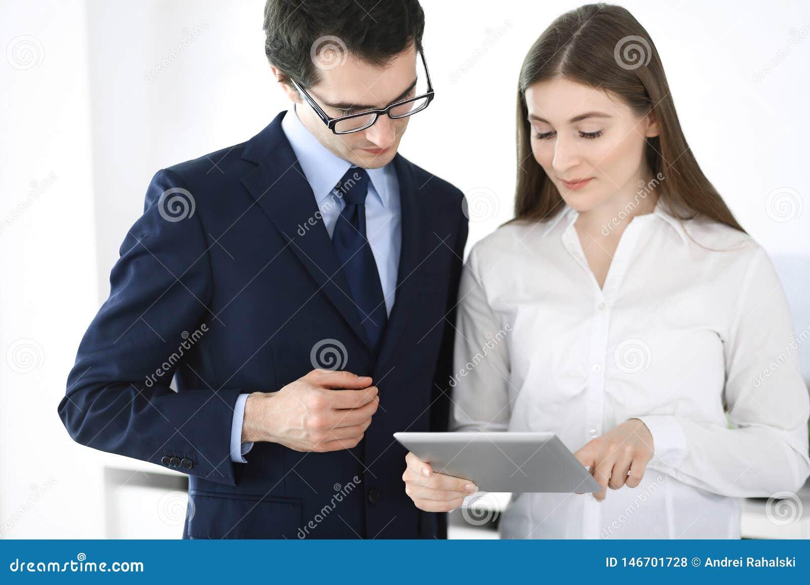 Biznesmeni i kobieta u?ywa pastylka komputer w nowo?ytnym biurze Koledzy lub firma kierownicy przy miejsce pracy partnery