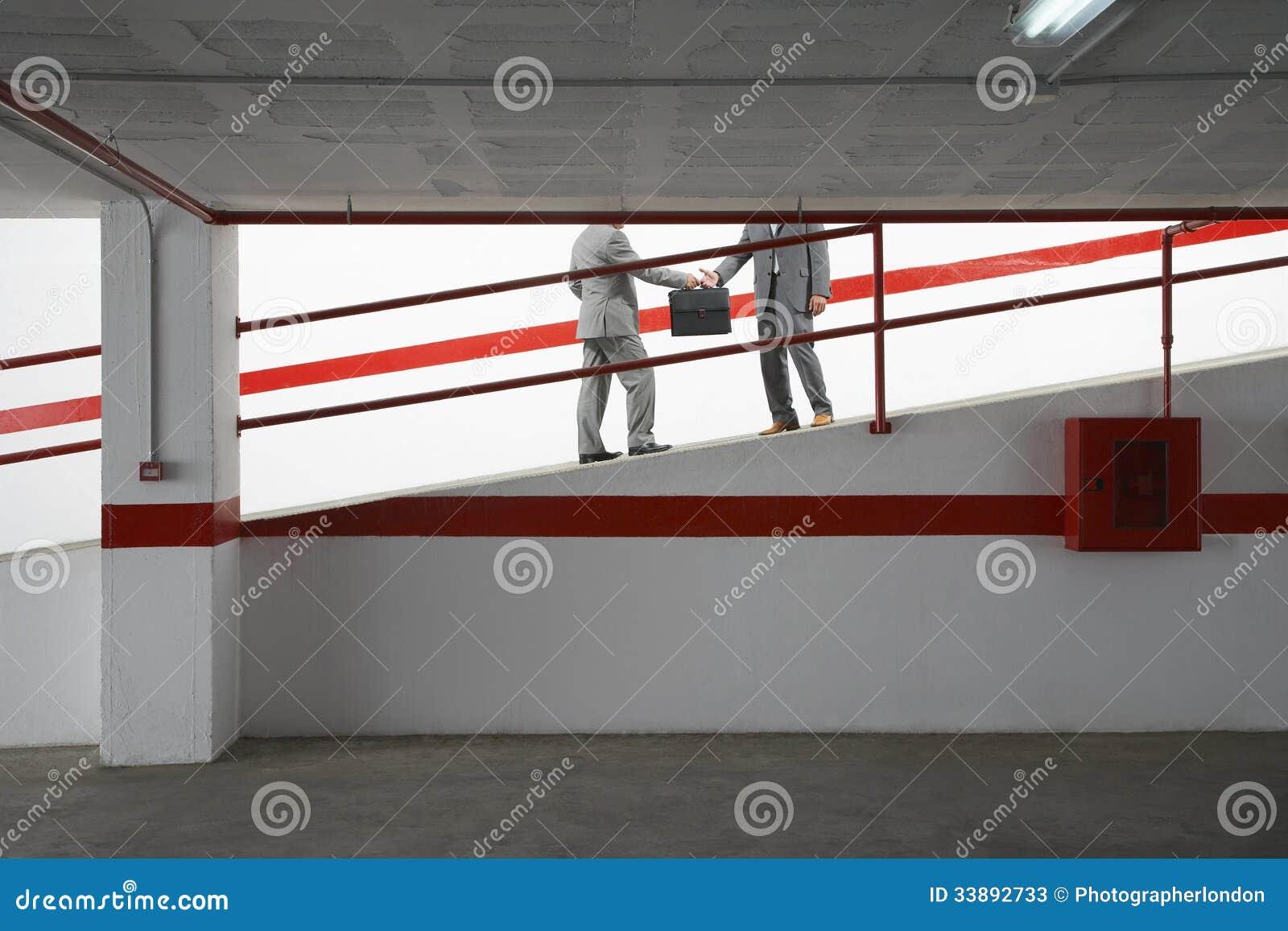Biznesmeni Wymienia teczkę Na rampie W garażu