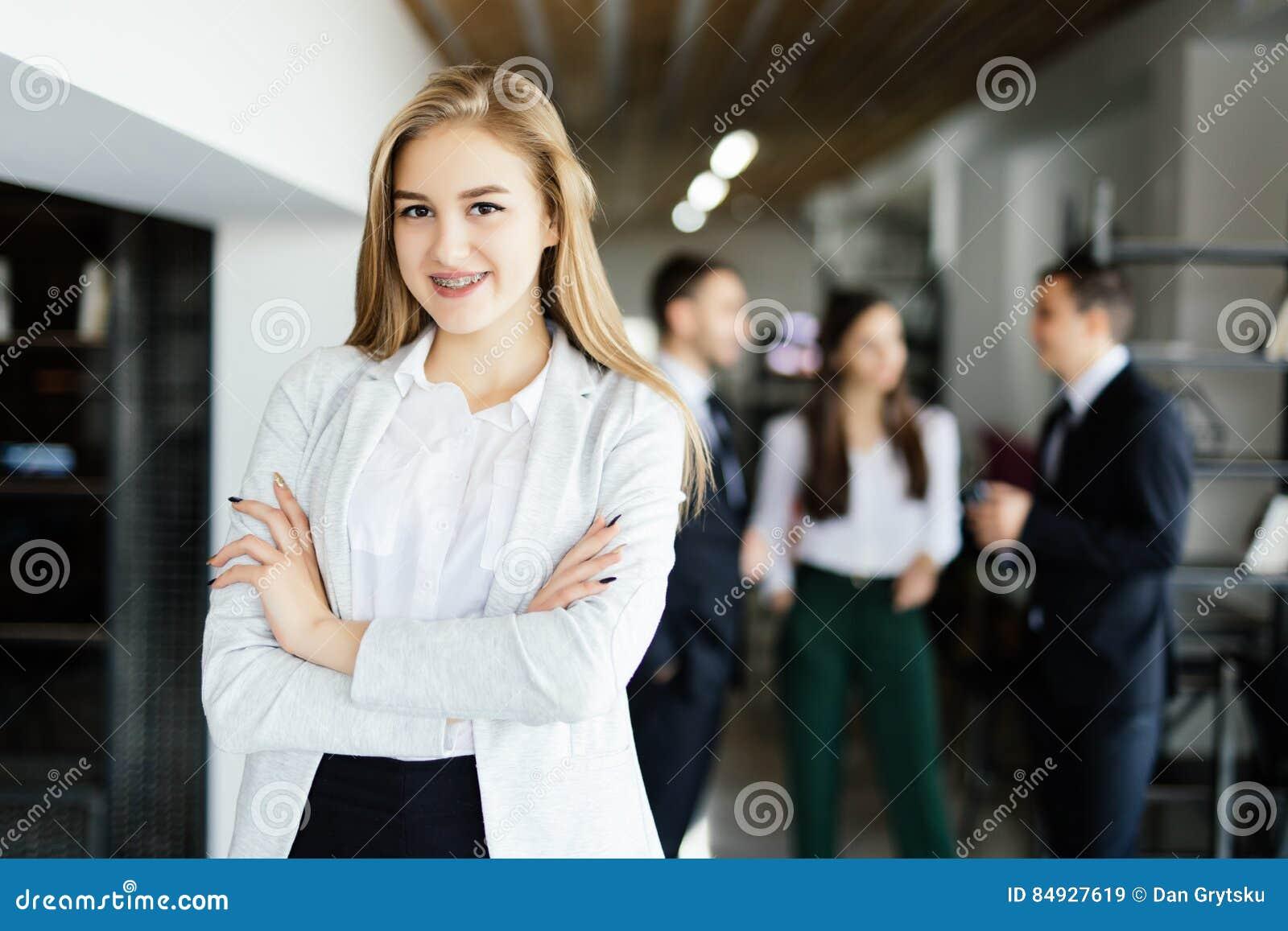 Biznesowa dama z krzyżować rękami przed dyskutować coworkers