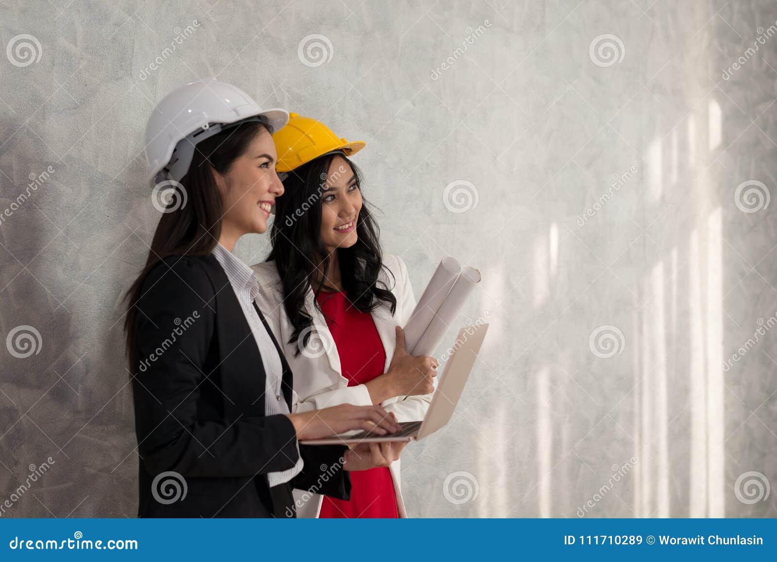 Biznesowa dziewczyna i inżynier z Azjatyckimi ludźmi pracujemy z laptopem ar