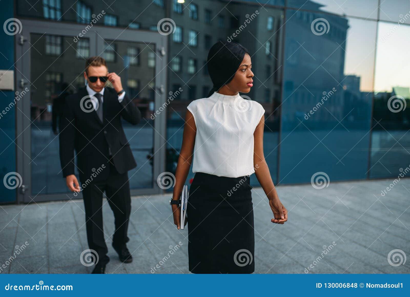 Biznesowa kobieta, ochroniarz w kostiumu na tle
