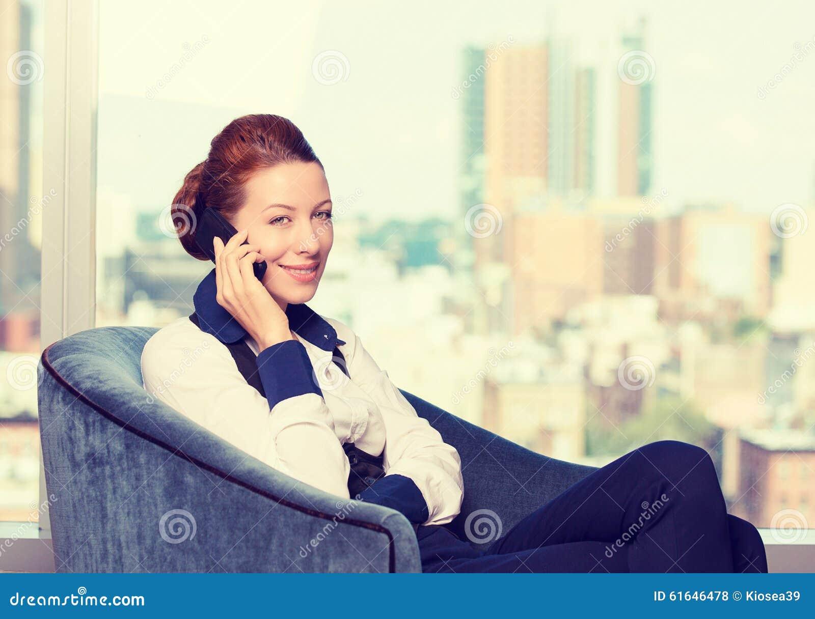 Biznesowa kobieta opowiada na telefonie komórkowym jest usytuowanym w karle biurowym okno