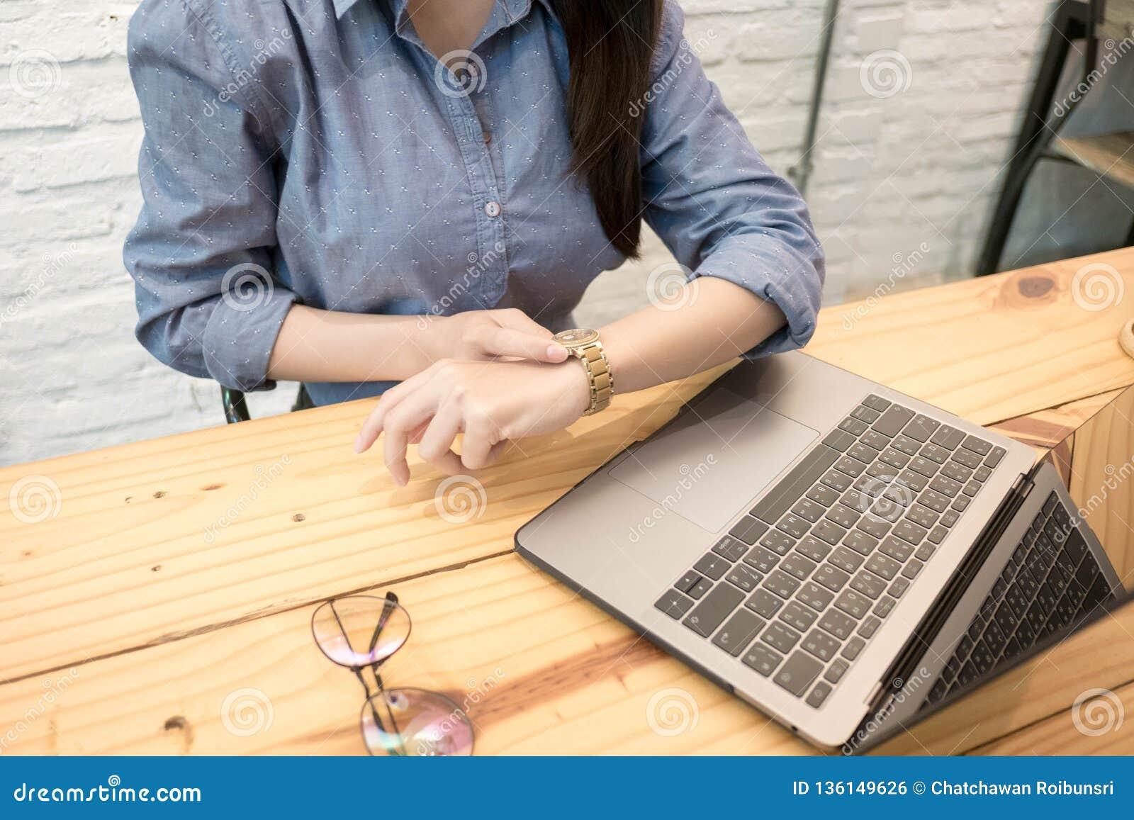Biznesowa kobieta pisać na maszynie na klawiaturze i ogląda przy jego wristwatch Pojęcie czasu zarządzanie