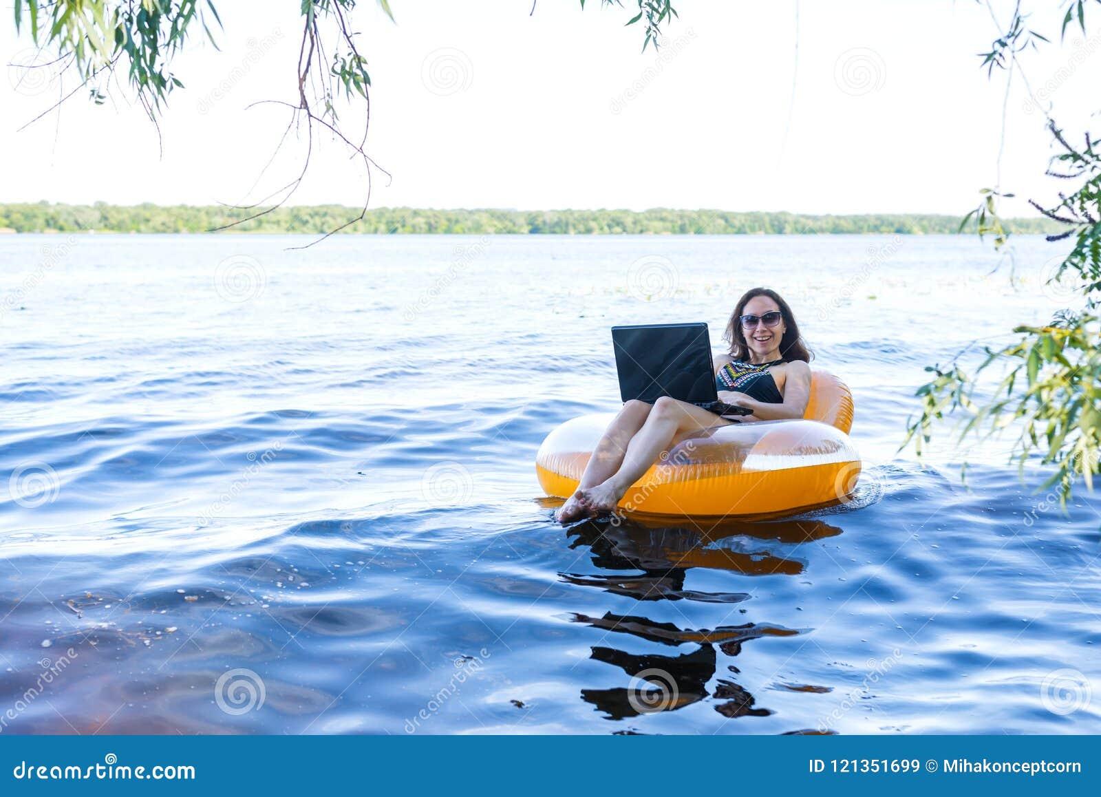 Biznesowa kobieta pracuje na laptopie w nadmuchiwanym pierścionku na rzece pojęcie pracować na wakacje