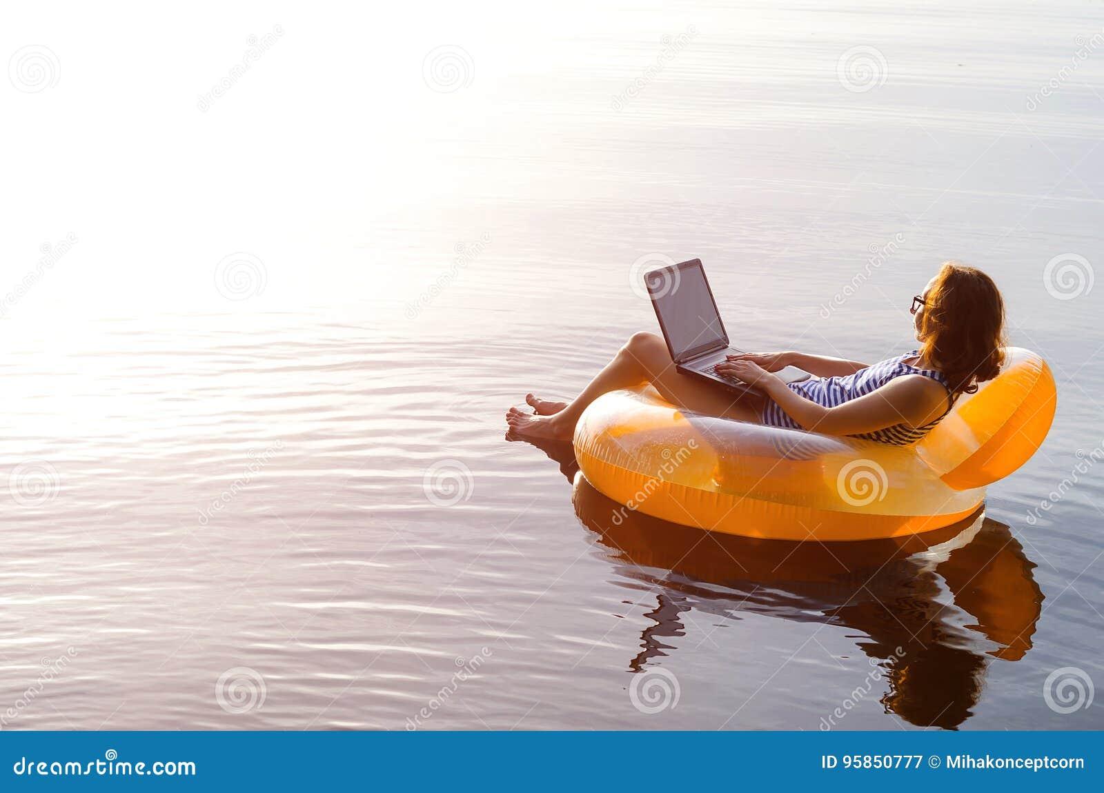 Biznesowa kobieta pracuje na laptopie w nadmuchiwanym pierścionku w