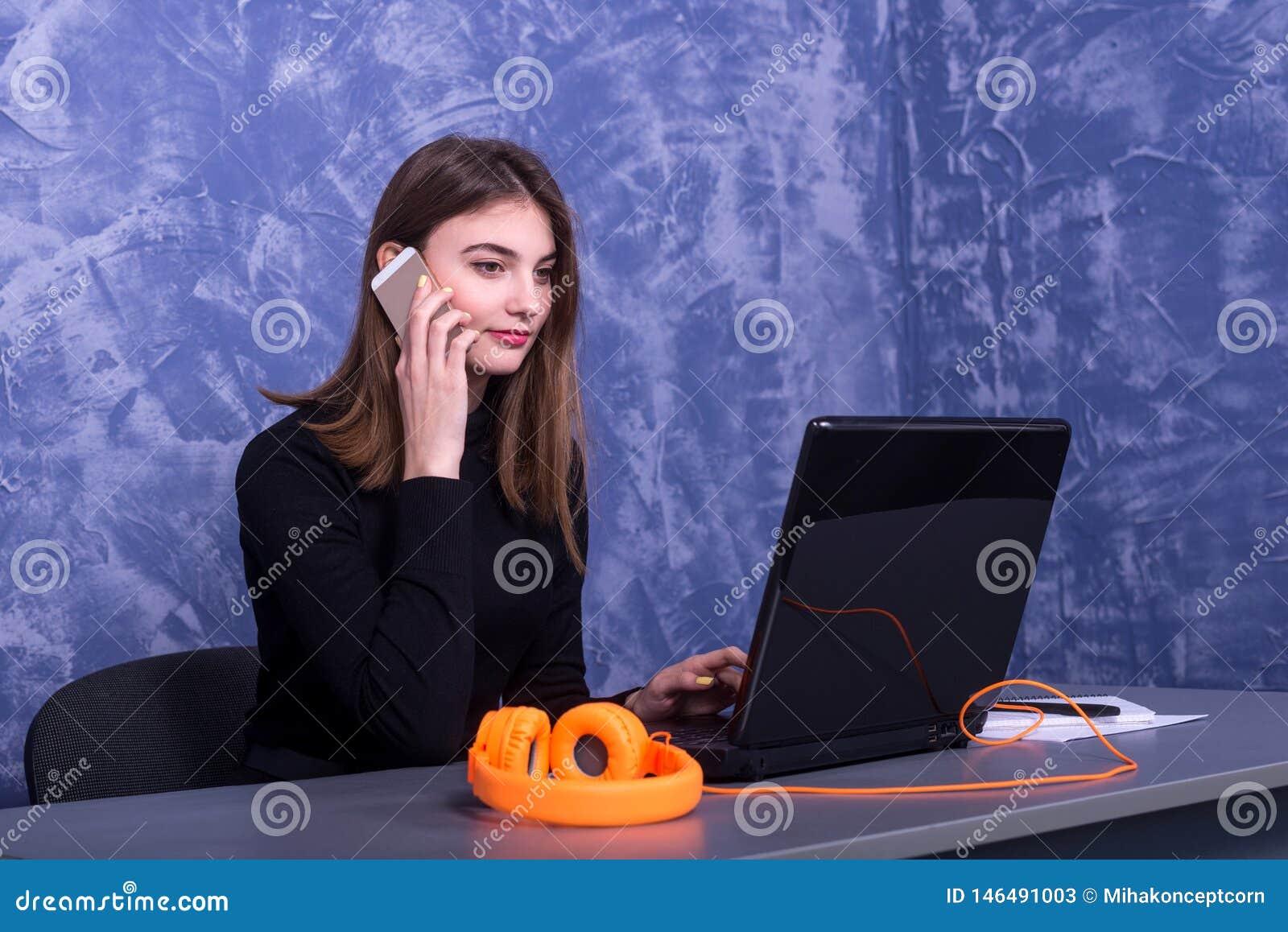 Biznesowa kobieta pracuje przy laptopem i opowiada na telefonie, odległa praca