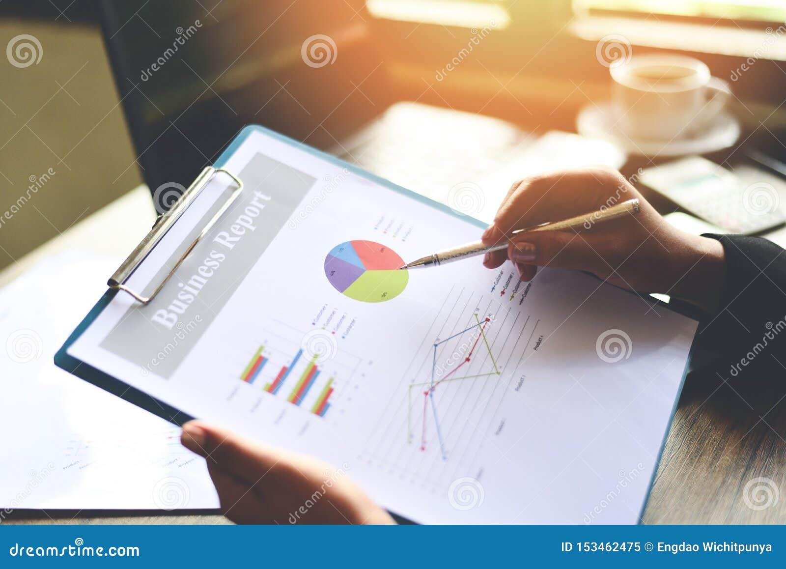 Biznesowa kobieta pracuje w biurze z sprawdzać biznesowego raport na stołowym biurku z kalkulator filiżanką i smartphone -