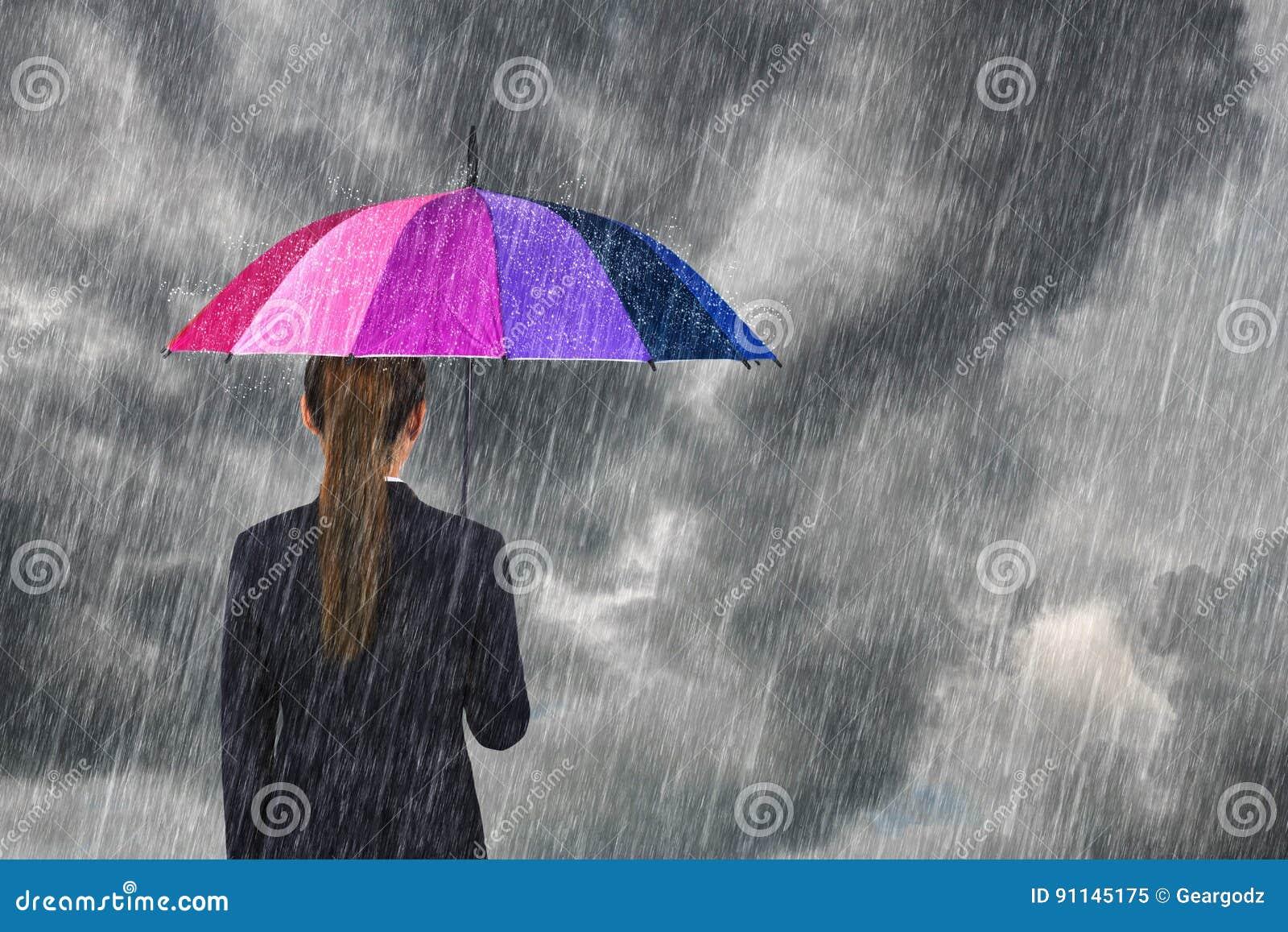 Biznesowa kobieta trzyma stubarwnego parasol pod niebem z spadkiem