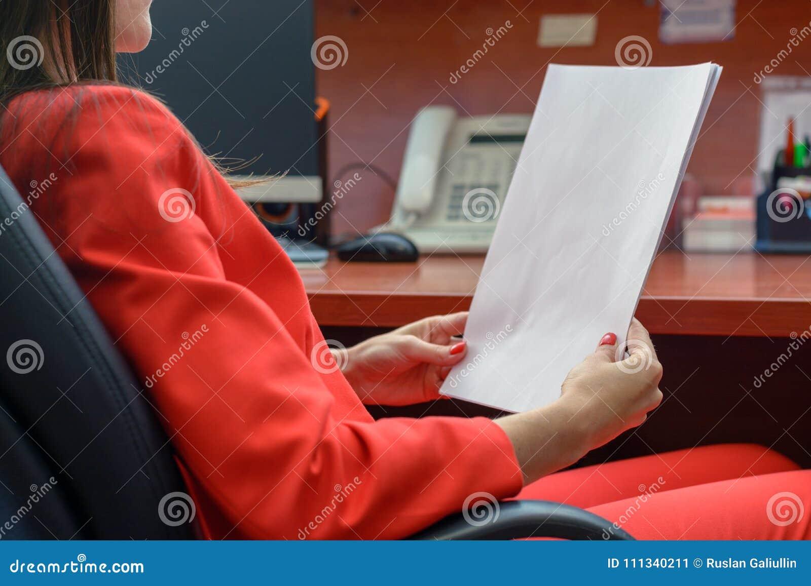 Biznesowa kobieta w czerwonym kostiumu siedzi w rzemiennym krześle czytaniu i kontrakt, sprawdza papier