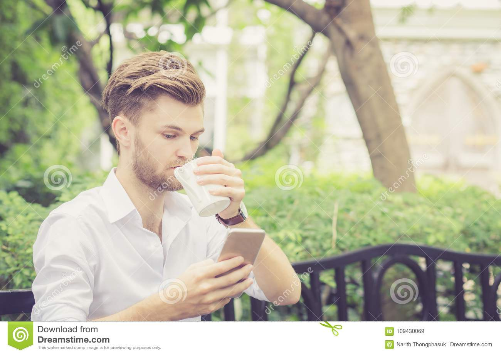 Biznesowa młoda przystojna mężczyzna napoju filiżanka kawy używać telefon komórkowego w parku