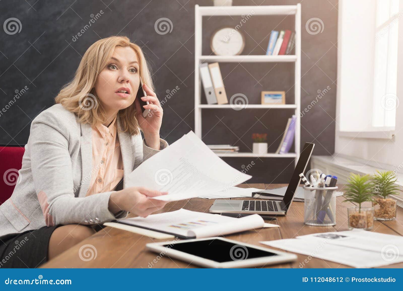 Biznesowa rozmowa, poważna kobieta konsultuje telefonem przy biurem