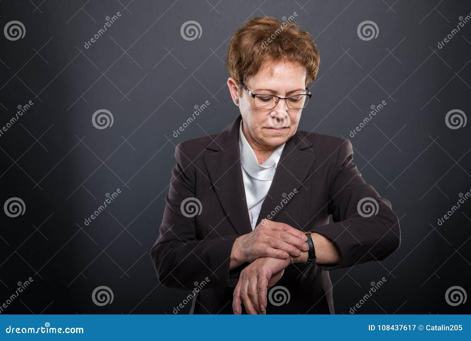 Biznesowa starsza dama sprawdza jej wristwatch