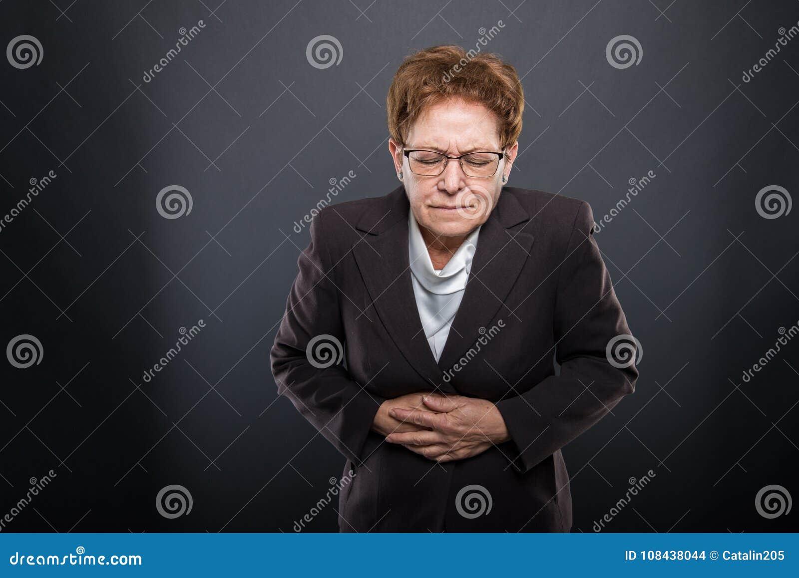 Biznesowa starsza dama trzyma jej żołądek jak kaleczenie