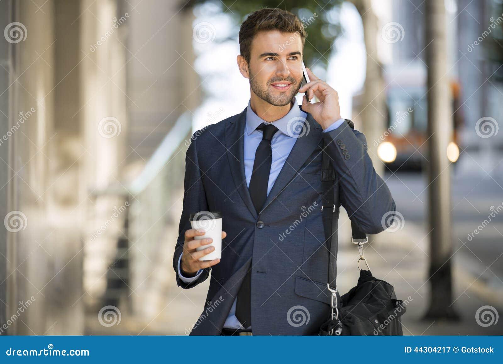Biznesowego mężczyzna odprowadzenie opowiada na telefonie komórkowym