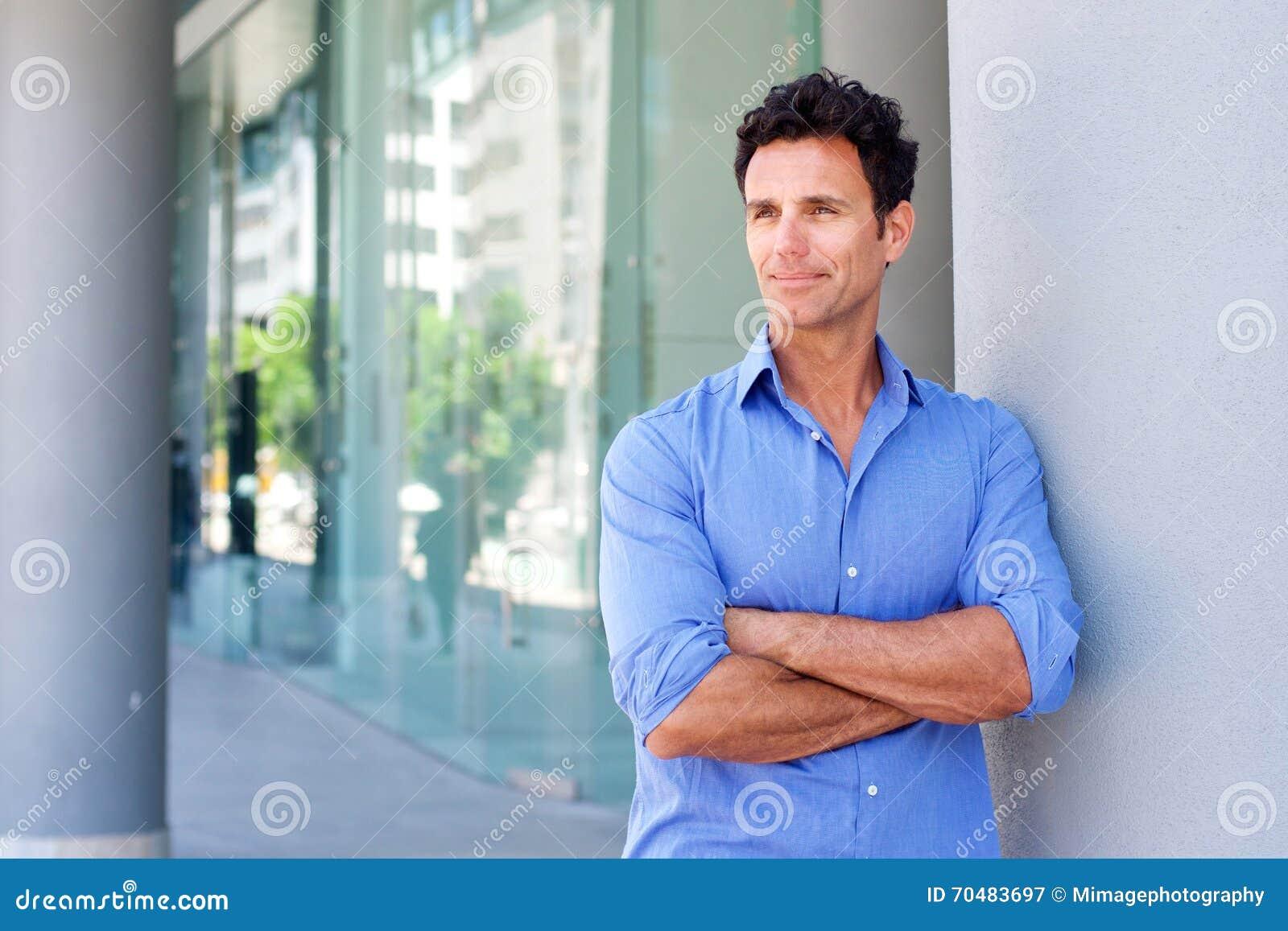 Biznesowego mężczyzna trwanie outside z rękami krzyżować