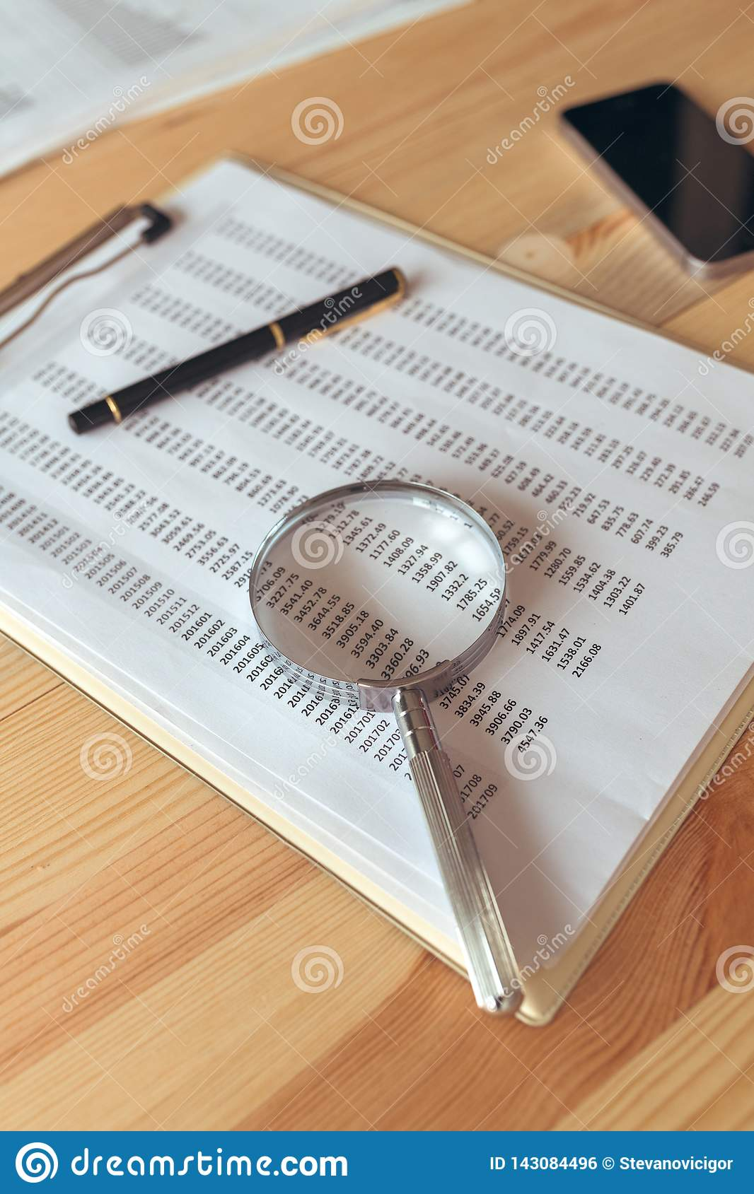 Biznesowego raportu analiza, powiększa - szkło nad papierowym spreadsheet