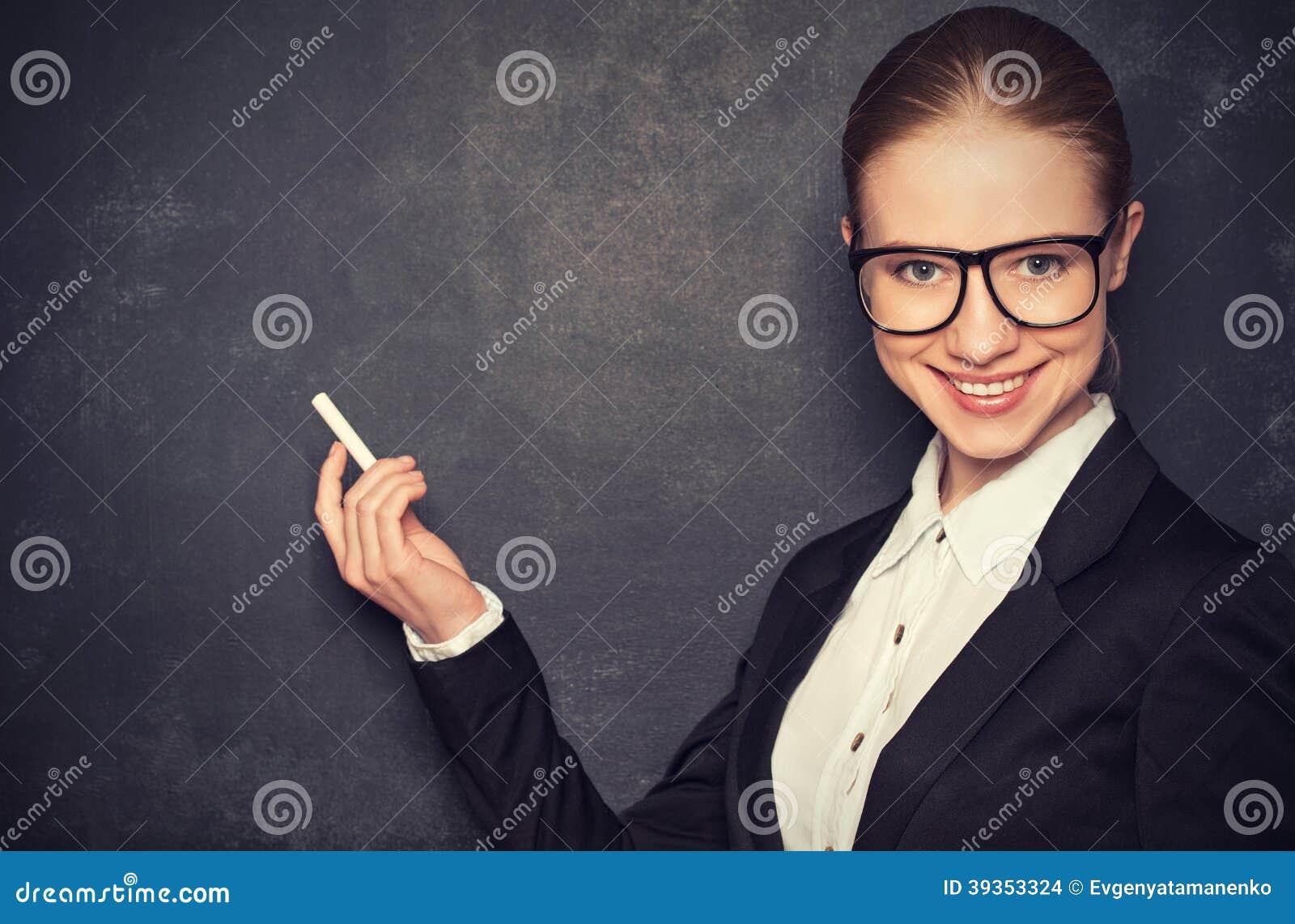 Biznesowej kobiety nauczyciel z szkłami i kostiumem z kredą   przy a
