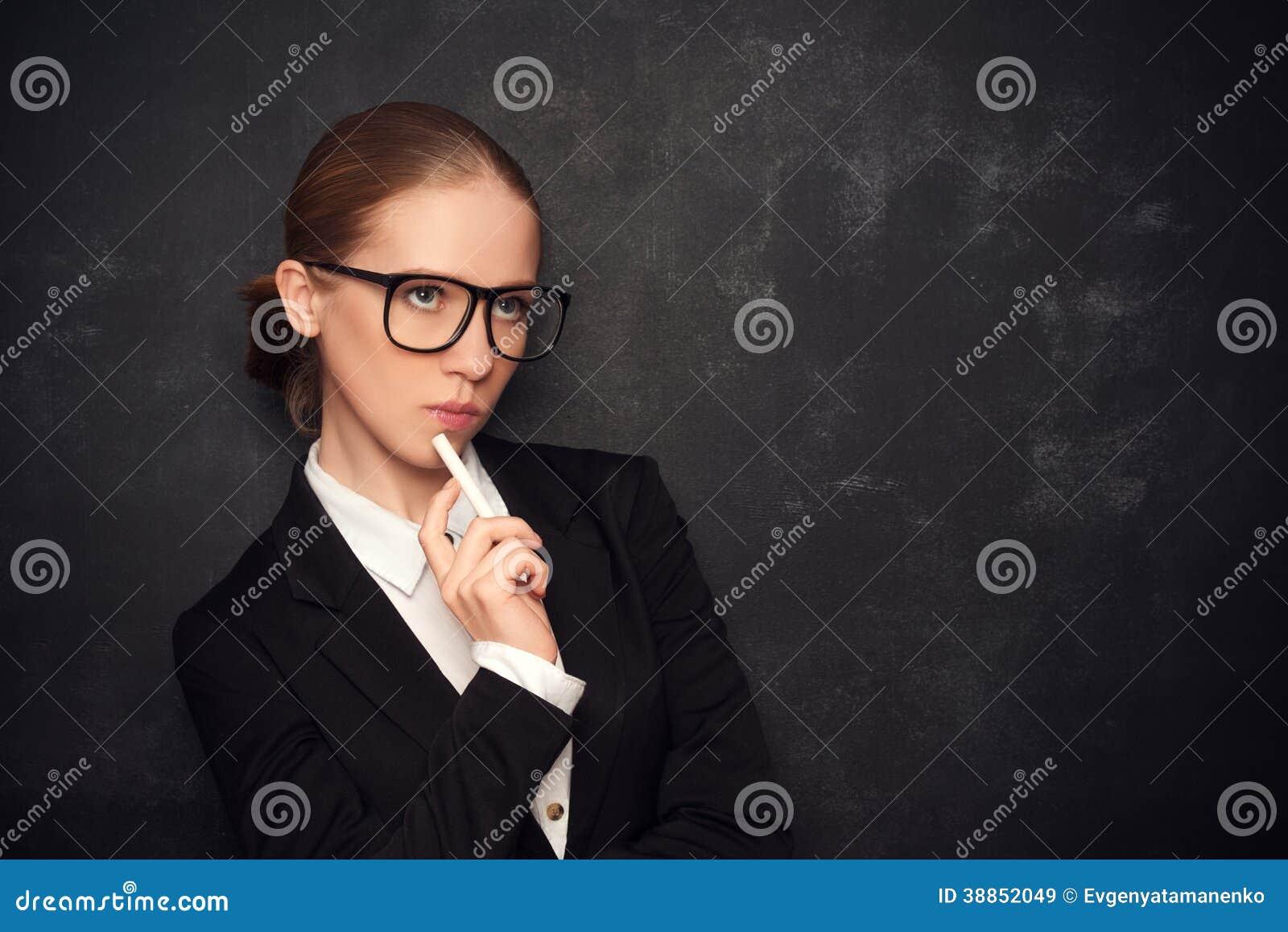 Biznesowej kobiety nauczyciel z szkłami i kredą