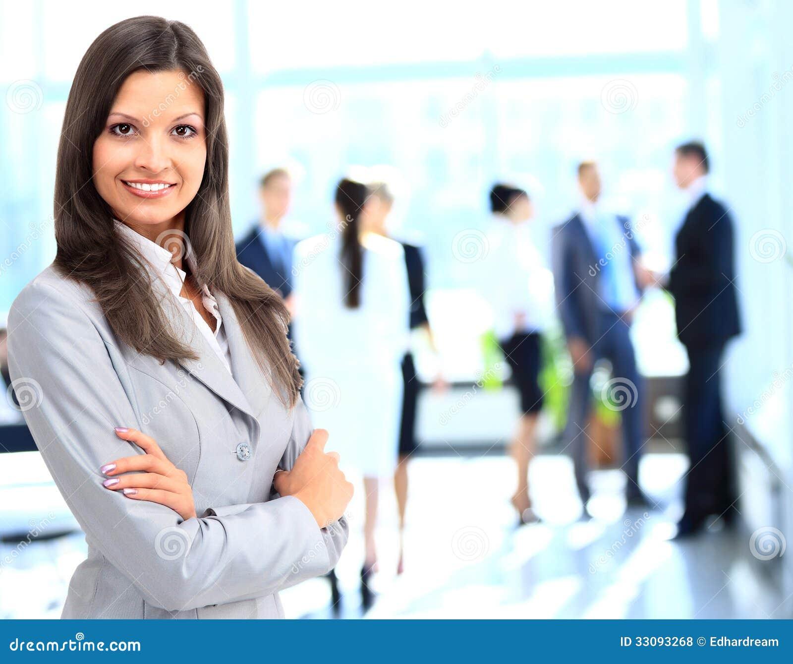 Biznesowej kobiety pozycja z jej personelem w tle przy biurem