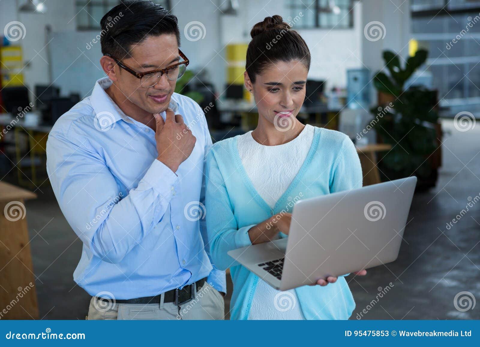 Biznesowi koledzy dyskutuje nad laptopem