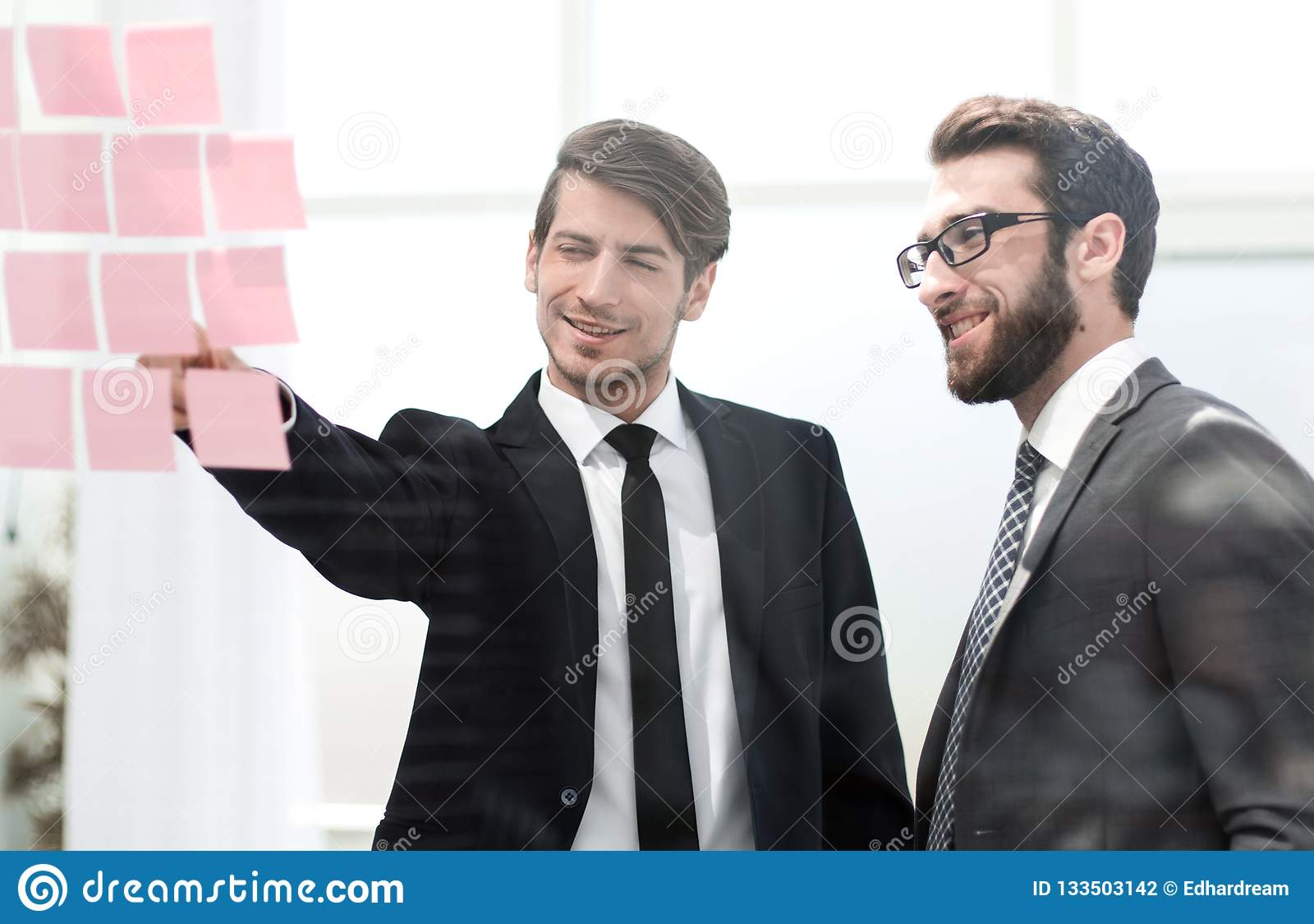 Biznesowi koledzy dyskutuje notatki na biuro desce