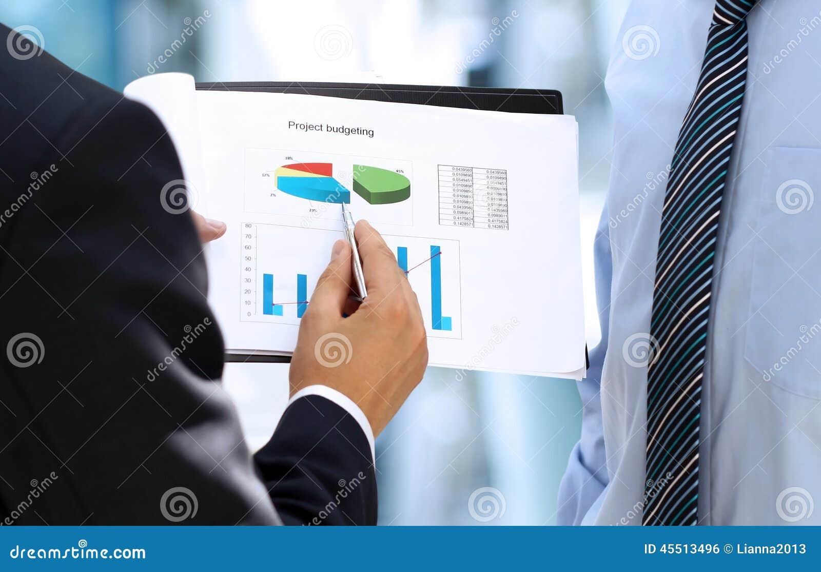 Biznesowi koledzy pracuje wpólnie i analizuje pieniężnej figi