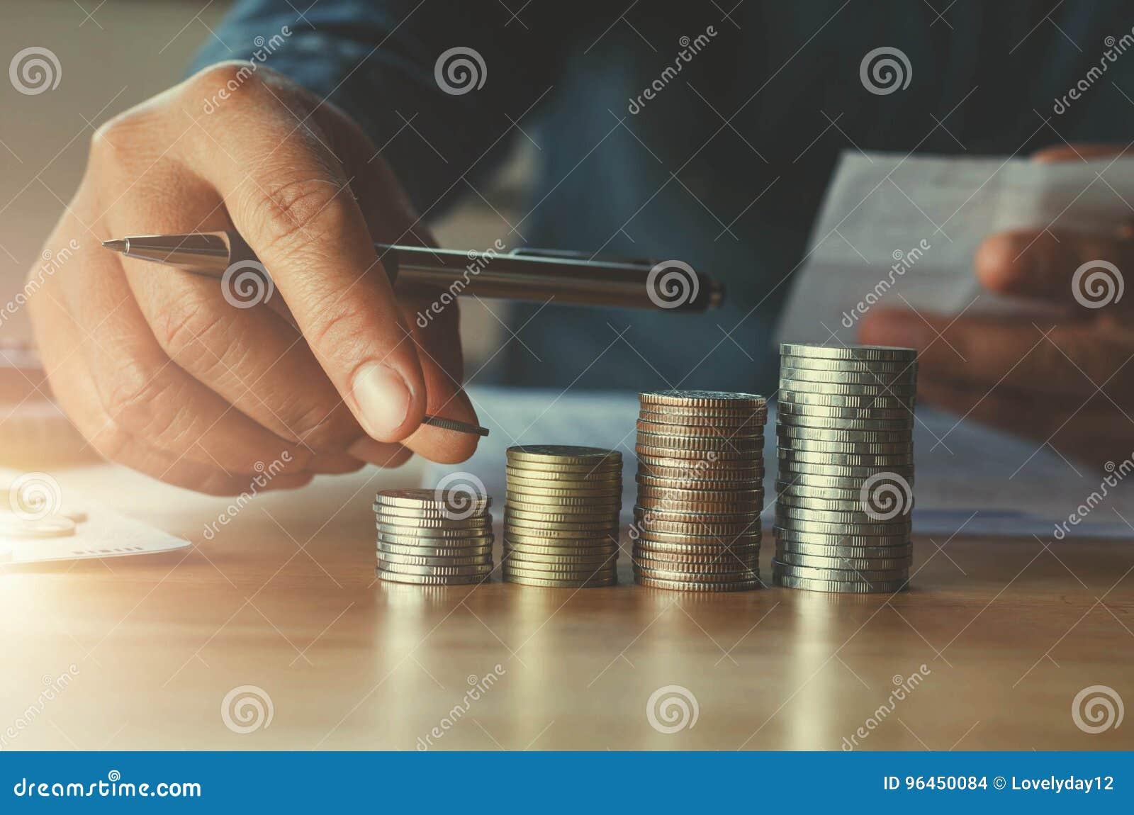 Biznesowy accountin z oszczędzanie pieniądze z ręki kładzenia monetami dalej